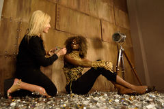 Artist applying makeup to model at photo shoot on floor in bright gold studio Royalty Free Stock Photo