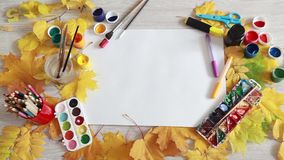 The artist arranges items for creativity on the table with autumn leaves. stock footage