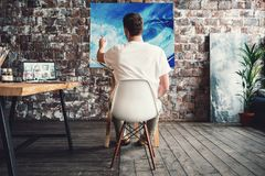 Artist in art studio sits on chair in front of canvas on easel and drawing. Painter work in workshop. Working process Stock Photo