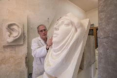 Artist in the art studio at work on sculpture Royalty Free Stock Photography