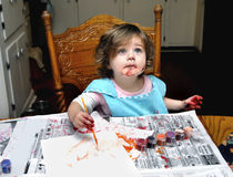 Artist and Artwork. Toddler has her first lesson in painting. She is intent and has paint smeared on face, hands and hair royalty free stock photography