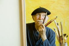 Artist with a Beret at a Canvas. Elderly painter wearing a beret working on a large canvas Royalty Free Stock Photos