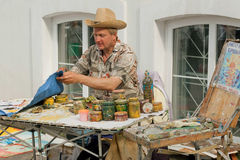 Artist in big hat working outdoor with paintings Stock Images