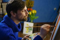 Artist paints on canvas. Artist in blue sweater paints with brushes on canvas. Flowers in the background Stock Photo