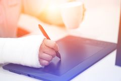 Artist with broken arm drawing something with graphic tablet. Hold pen in broken fractured arm in plaster cast. Artist with broken arm drawing something with royalty free stock photography