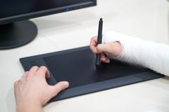 Artist with broken arm drawing something with graphic tablet. Hold pen in broken fractured arm in plaster cast. Artist with broken arm drawing something with royalty free stock images