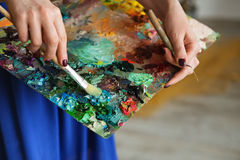 artist brush mix color oil painting on palette is holding in her Stock Photo