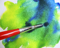 Artist Brush on Watercol.Paper. Artist brush prepairs wet artist paper with watercolor background Stock Images