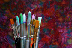 Artist brushes. A collection of artist brushes against an original abstract background Stock Photos