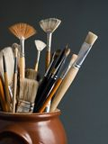 Artist brushes. In a pot, on a dark grey background royalty free stock photos