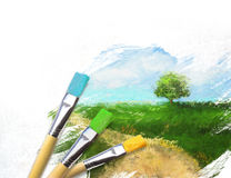 Artist brushes with a half finished painted canvas. Of rural landscape stock photos