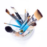 Artist brushes in a jar. Artist brushes in a glass jar - view from the top. Isolated over white background royalty free stock image