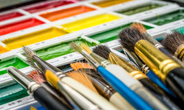 Artist Brushes and Palette. A collection of artist's brushes on a watercolour paint palette Stock Photography