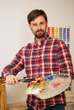 Artist with brushes and palette. Man artist holds in his hands a paintbrush and a wooden palette with oil paints. Portrait Royalty Free Stock Images
