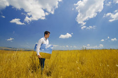 Artist with canvas in hand on a field. Young artist walking in a field with a canvas paint containing an image of himself Stock Photo