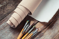 Artist canvas in roll and paintbrushes on table Stock Photo