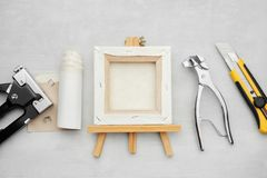 Artist canvas on wooden easel, canvas in roll, canvas stretcher pilers, knife and staple gun on marble background. Painters supplies. Top view royalty free stock photography