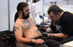 An artist carefully designs tattoo on at the 4 Arts Fest on April 16, 2016 in Sofia, Bulgaria Royalty Free Stock Images