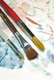 Artist Choice of Brush. Three different watercolor paintbrushes are laid out on a color mixing piece of paper Royalty Free Stock Image