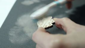 An artist cleans with brush a wooden craft after grinding on sandpaper.  stock video