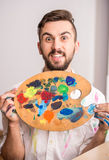 Artist. Close-up of young artist with palette is looking at the camera Royalty Free Stock Photos