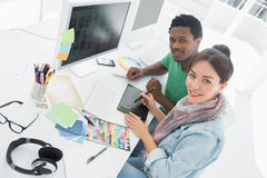 Artist with colleague drawing something on graphic tablet stock photography