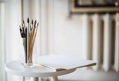 Artist& créatif x27 ; espace de travail de s, pinceaux artistiques et papier Photos stock