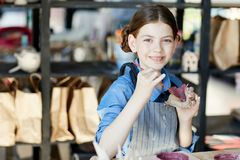 Artist or craftsperson. Cheerful kid in apron painting in purple self-made clay mug at lesson of crafts royalty free stock image