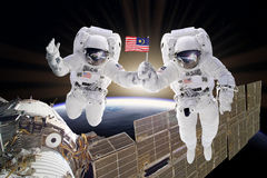 Artist creative edit composite depicting teamwork on ISS. Astronauts floats on space sunrise holding USA flag. Artist creative edit composite depicting stock photo