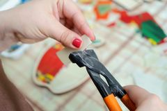 Female hands artist collect mosaic close up. The artist cuts glass and maker mosaic in a wooden harvesting. Female hands closeup collect mosaic of colored stones stock photos
