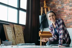 Artist delight woman canvas artworks art supplies. Artist delight. Smiling woman with canvas and palette knife sitting on floor and looking at camera. Artworks royalty free stock photos
