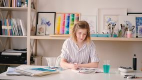 Artist delight watercolor artwork paint brush. Artist delight. Smiling pleased blonde female applying paint with brush. Watercolor artwork in process. Tidy stock video footage