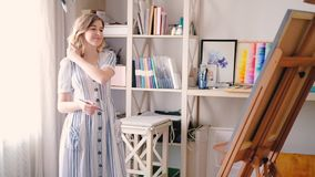 Artist delight female canvas easel inspiration. Artist delight. Young blonde female pleased content looking at canvas on easel. Inspiration creativity. Cozy home stock video footage