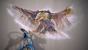 Artist designer draws an eagle on the wall. Craftsman decorator paints a picture with acrylic oil color. Painter painter. Dressed in a paint coat. Indoor. Dark stock video footage