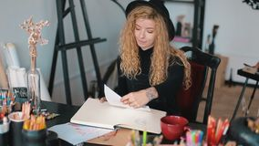 Artist at the desk. Professional artist working at the desk full of coloured pencils, having a mug of tea while drawing a sketch in the album, artistic working stock footage