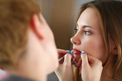 Artist doing professional make up of woman Stock Image