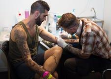 Artist  doing  tattoo on client hand Stock Photo