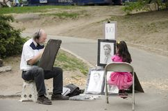 Artist draftsman drawing portrait of a young girl in Central Park, NYC. New York City, USA - May 05, 2015: an artist draftsman drawing portrait of a young girl stock photos
