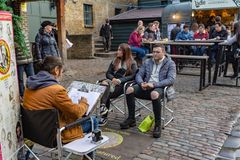 Artist drawing caricatures of an British couple in Camden Lock Market or Camden Town in London,. London, UK - 20, December 2018: Artist drawing caricatures of an stock photos