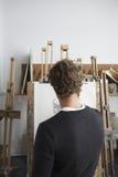 Artist Drawing Charcoal Portrait In Studio. Rear view of a male artist drawing charcoal portrait in studio Stock Photos
