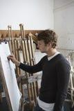 Artist Drawing Charcoal Portrait In Studio. Side view of a male artist drawing charcoal portrait in studio Stock Photos
