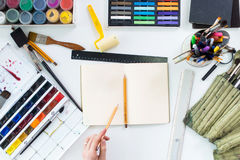 Artist drawing graphic sketch at sketchbook. Workplace, workspace. Top view photo of artistic tools lying on work-table. Gouache, crayons palette and royalty free stock photos