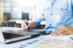 Artist drawing on graphic tablet with color swatches in office. Architectural drawing with work tools and accessories royalty free stock photos