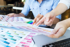 Artist drawing on graphic tablet with color swatches in office. Graphic design and color swatches and pens on a desk. Architectural drawing with work tools and royalty free stock photo