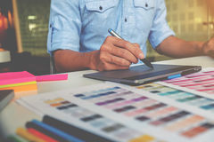 Artist drawing on graphic tablet in office. Graphic design and color swatches and pens on a desk. Architectural drawing with work tools and accessories Royalty Free Stock Images