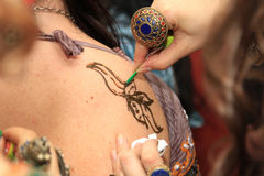 Artist drawing henna tattoos. Artist drawing henna tattoos on the body of a woman stock photo