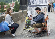 Artist drawing a portrait, raw. Street artist drawing young lady's portrait in Prague, raw Royalty Free Stock Image
