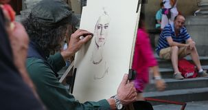 Artist drawing a portrait of a young woman with pastels and an easel. Florence, Italy - August 31, 2019: Street male artist drawing a portrait of a young woman stock footage