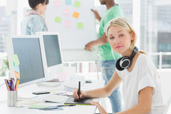 Artist drawing something on graphic tablet with colleagues behind at office. Side view of an artist drawing something on graphic tablet with colleagues behind at Royalty Free Stock Photos