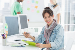 Artist drawing something on graphic tablet with colleagues behind. Portrait of an artist drawing something on graphic tablet with colleagues behind at the office Royalty Free Stock Photo